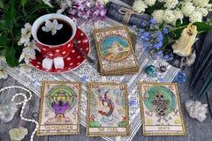 Tarotkaarten met kop thee, bloemen en zwarte kaarsen op planken royalty-vrije stock foto's