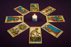 Tarots. Tarot cards around a candle on purple background Stock Images