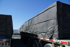 Tarp Covered Cargoes on Tractor Trailers. Cargoes covered with black tarps on the commercial tractor trailers ready to go Royalty Free Stock Photos
