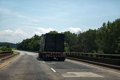 Tarp Covered Semi Freight on Highway. Semi truck hauling tarp-covered cargo under blue sky Royalty Free Stock Photos
