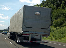 Tarp-Covered Semi Truck on Highway. Rear and side view of tarp-covered semi truck on interstate Stock Image