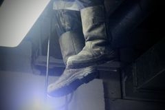 Tarpaulin boots in the light of a lantern during the works. Work of industrial clean of sewage, plumbing in the building. royalty free stock photography