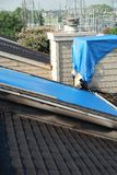 Tarpaulins on roof and chimney. Blue tarpaulins cover holes in an apartment building roof, and a chimney stack.  Scorch marks from a fire mark the eaves Stock Photography