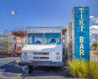 TARPON SPRINGS, FLORIDA - JUNE 30, 2019: Tiki Bar sign next to a beat up old white ice cream truck royalty free stock photography