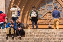 TARRAGONA, ESPAÑA - 1 DE MAYO DE 2017: Una mujer y un hombre se están sentando en los pasos de la catedral del católico de la cat Fotografía de archivo libre de regalías