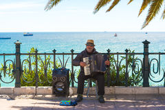 TARRAGONA, SPAIN - MAY 1, 2017: Musician on the waterfront plays the accordion. Copy space for text. Royalty Free Stock Image
