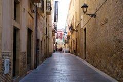 TARRAGONA SPANIEN - AUGUSTI 28th, 2017: Öde gata av den gamla europeiska staden på en klar solig dag De ljusa väggarna av Royaltyfri Bild