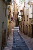 TARRAGONA SPANIEN - AUGUSTI 28th, 2017: Öde gata av den gamla europeiska staden på en klar solig dag De ljusa väggarna av Arkivbild