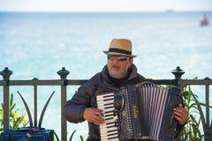 TARRAGONA, SPANJE - MEI 1, 2017: De musicus op de waterkant speelt de harmonika Exemplaarruimte voor tekst stock foto