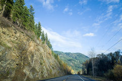 Tarred road through scenic mountains. Passing a deep rock cutting forested with evergreen conifers as it recedes straight into the distance stock photo