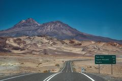Tarred road with signpost and rugged mountains stock images