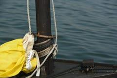 Tarred Sailboat Mast. With yellow wrapped sail Royalty Free Stock Photo