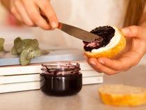 Tarro abierto con el atasco delicioso de la grosella negra Foto de archivo