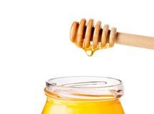 Tarro abierto de la miel en el fondo blanco con el cazo de madera de la miel en el top con la miel del descenso Fotografía de archivo libre de regalías