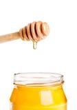Tarro abierto de la miel en el fondo blanco con el cazo de madera de la miel en el top con la miel del descenso Foto de archivo