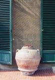 Tarro antiguo de la arcilla que hace una pausa la pared de una casa vieja en Italia imagen de archivo libre de regalías