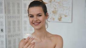 Tarro atractivo de la abertura de la mujer joven con crema en el cuarto de ba?o blanco metrajes