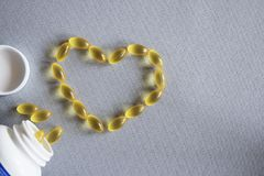 Tarro blanco con las cápsulas amarillas dispersadas de vitaminas en una tela gris Imagen de archivo libre de regalías