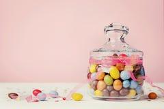 Tarro colorido del caramelo adornado con la cinta del arco contra fondo rosado Imagen de archivo