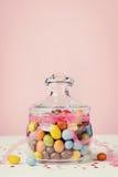 Tarro colorido del caramelo adornado con la cinta del arco contra fondo rosado Fotos de archivo libres de regalías