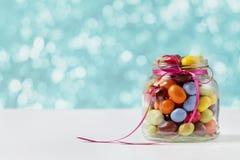 Tarro colorido del caramelo adornado con un arco contra fondo azul del bokeh Imagen de archivo libre de regalías