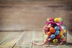 Tarro colorido del caramelo adornado con un arco contra fondo de madera rústico Fotos de archivo