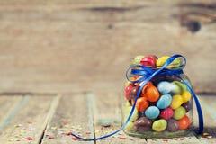 Tarro colorido del caramelo adornado con un arco contra fondo de madera rústico Imagen de archivo