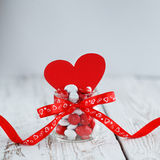 Tarro colorido del caramelo adornado con un arco rojo y un corazón de papel rojo en el fondo de madera blanco Concepto del día de Fotografía de archivo