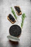 Tarro con el caviar y los bocadillos negros Foto de archivo