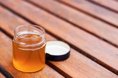 Tarro con la mermelada de la miel o de la fruta del color de oro foto de archivo