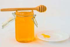 Tarro con la miel en un fondo blanco Cazo del oney del  de Ð en el tarro Foto de archivo