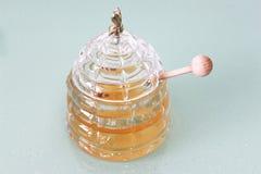 Tarro con la miel y el palillo de madera Fotografía de archivo libre de regalías