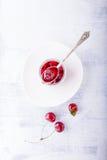Tarro de atasco de cereza y de algunas cerezas en la tabla Fotos de archivo libres de regalías