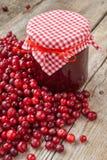 Tarro de atasco y de arándanos rojos frescos en la tabla de madera Fotos de archivo libres de regalías