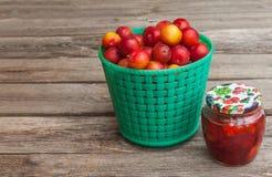 Tarro de atasco y una cesta con los ciruelos rojos Imagenes de archivo