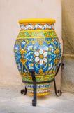 Tarro de cerámica adornado con los adornos florales puestos en un pie Imagen de archivo