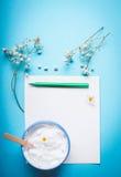 Tarro de crema con las flores y la espátula en el papel en blanco con la pluma para la nota o la lista en fondo azul Cosmet herba imagenes de archivo