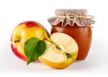 Tarro de cristal de atasco hecho en casa de la manzana con las frutas jugosas frescas bajo la forma de ingredientes Imagenes de archivo