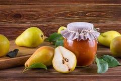 Tarro de cristal de atasco hecho en casa de la pera con las frutas frescas y los ingredientes Imagen de archivo