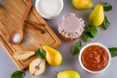 Tarro de cristal de atasco hecho en casa de la pera con las frutas frescas y los ingredientes Fotografía de archivo