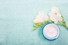 Tarro de cristal azul con el facial o la crema corporal en el fondo de la toalla Imagen de archivo