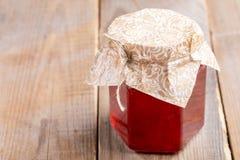 Tarro de cristal cerrado del primer con la mermelada de fresa hecha en casa en la tabla de madera vieja fotografía de archivo libre de regalías