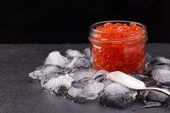 Tarro de cristal con el caviar de color salmón que se coloca en el medio de los cubos de hielo en la placa negra de la pizarra Foto de archivo libre de regalías