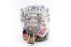 Tarro de cristal con el dinero y cadena cerrada Fotografía de archivo libre de regalías