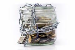 Tarro de cristal con el dinero y la cadena bloqueada Foto de archivo libre de regalías