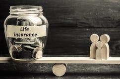 Tarro de cristal con el dinero y seguro de vida de las palabras el 'y la familia en las escalas El concepto de seguro médico de l imágenes de archivo libres de regalías