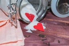 Tarro de cristal con el interior del azúcar adornado con el corazón de la tarjeta del día de San Valentín Foto de archivo