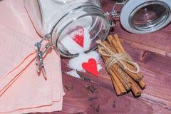 Tarro de cristal con el interior del azúcar adornado con los palillos del corazón y del canela de la tarjeta del día de San Valen Imagen de archivo libre de regalías