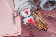 Tarro de cristal con el interior del azúcar adornado con los palillos del corazón y del canela de la tarjeta del día de San Valen Foto de archivo