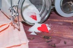 Tarro de cristal con el interior del azúcar adornado con los palillos del corazón y del canela de la tarjeta del día de San Valen Imágenes de archivo libres de regalías